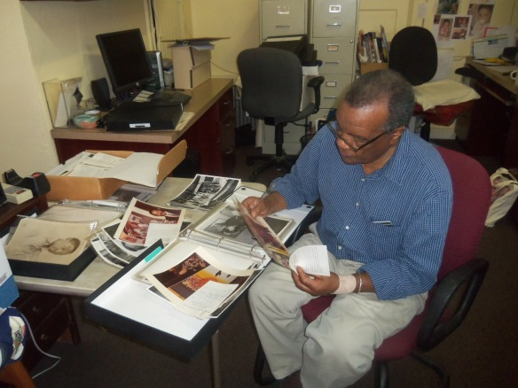 David C. Driskell at his home helping to identify photographs in his collection. David C. Driskell Center Archive. November 19, 2014.